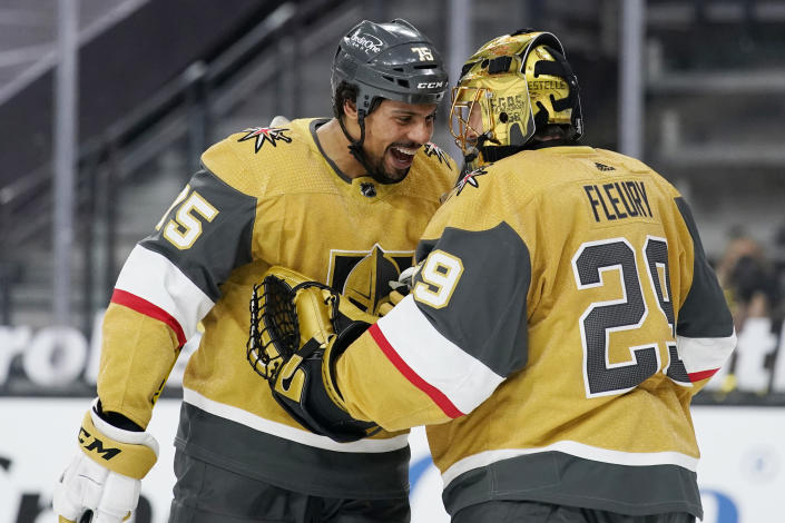 Vegas Golden Knights goaltender Marc-Andre Fleury, right, celebrates after right wing Ryan Reaves, left, scored against the San Jose Sharks, during the third period of an NHL hockey game Wednesday, March 17, 2021, in Las Vegas. (AP Photo/John Locher)