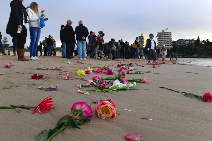 <em>Family and friends gather on Sydney's Freshwater Beach to throw flowers into the sea in memory of Justine (AP)</em>