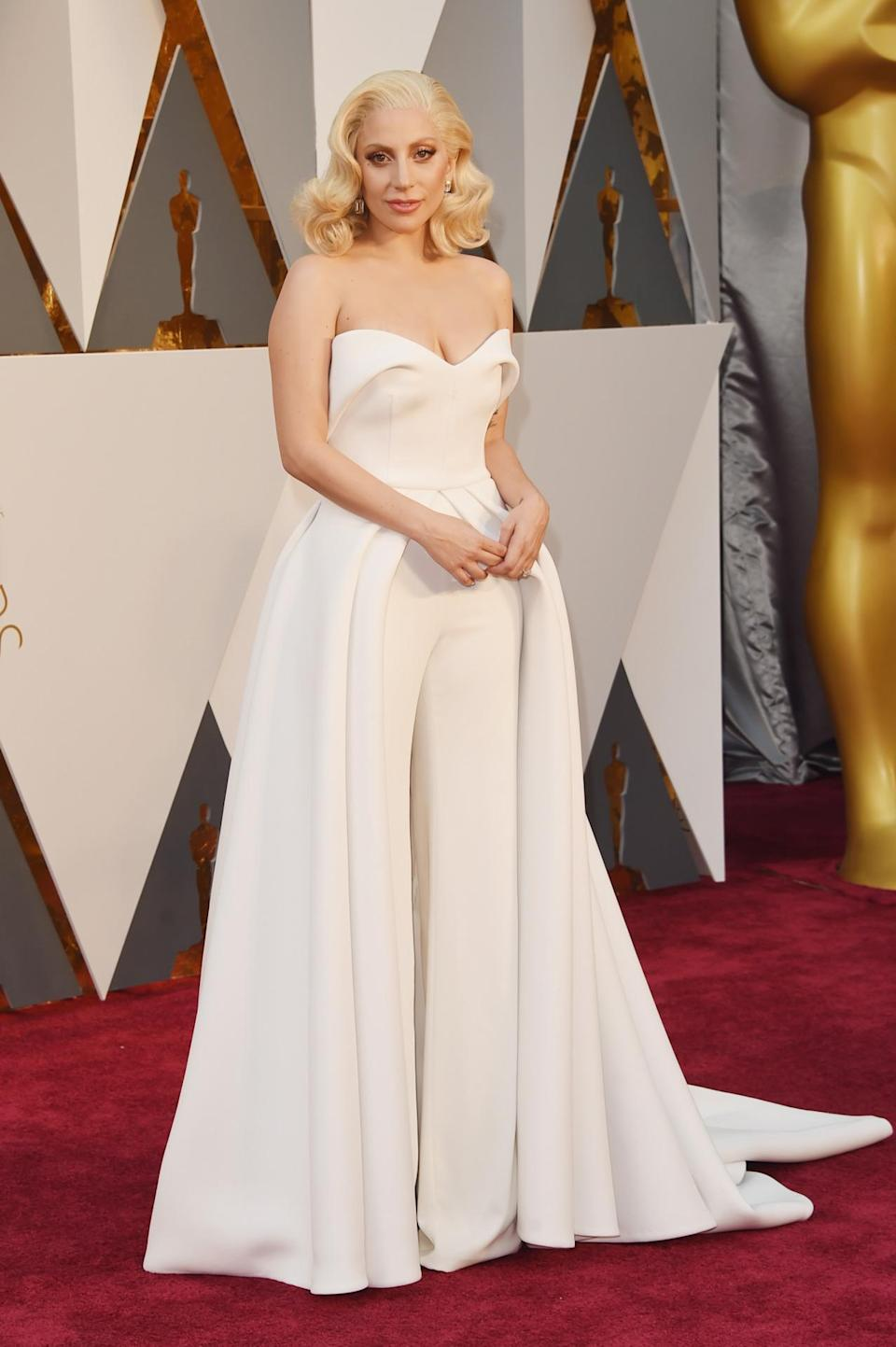 """<p>Wearing a white jumpsuit with a train, Lady Gaga brought innovation to the red carpet. Not only did the piece look amazing on the singer, it also made her feel confident. """"I never thought anyone would ever love me because I felt like my body was ruined by my abuser,"""" Gaga shared in an Instagram post from the ceremony alongside a photo of her kissing her fiancé, Taylor Kinney. """"But he loves the survivor in me. He's stood by me all night proud and unashamedly. THATS a real man."""" <i><i>(Photo: Getty Images)</i></i></p>"""