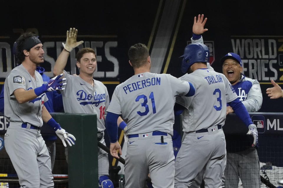 Los Angeles Dodgers' Chris Taylor celebrates at the dugout after scoring on a single by Corey Seager during the eighth inning in Game 4 of the baseball World Series against the Tampa Bay Rays Saturday, Oct. 24, 2020, in Arlington, Texas. (AP Photo/Tony Gutierrez)