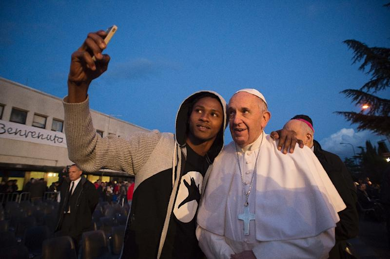 Pope Francis poses for a selfie with a migrant during his visit to the Castelnuovo di Porto refugee centre near Rome (AFP Photo/)