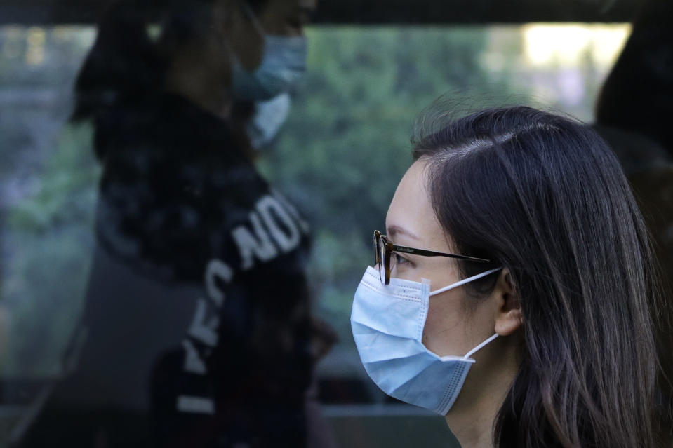 Commuters wearing face masks to help curb the spread of the coronavirus walk out from a subway station in Beijing, Monday, Oct. 19, 2020. (AP Photo/Andy Wong)