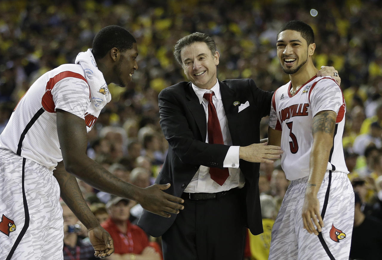 Louisville head coach Rick Pitino and Louisville guard Peyton Siva (3) reacts after Louisville defeated Michigan during the second half of the NCAA Final Four tournament college basketball championship game Monday, April 8, 2013, in Atlanta. Louisville won 82-76.(AP Photo/David J. Phillip)