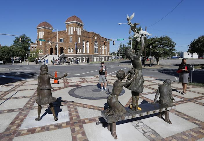 A newly unveiled statue honoring four slain young church girls graces the corner of Kelly Ingram Park, across the street from the 16th Street Baptist Church in Birmingham, Ala., Sunday, Sept. 15, 2013. The congregation gathered outside the church for the wreath laying ceremony at the spot where a bomb was detonated 50 years ago by the Ku Klux Klan, killing four young girls. (AP Photo/Hal Yeager)
