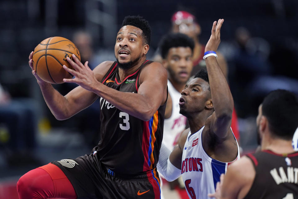 Portland Trail Blazers guard CJ McCollum (3) makes a layup as Detroit Pistons guard Hamidou Diallo (6) defends during the first half of an NBA basketball game, Wednesday, March 31, 2021, in Detroit. (AP Photo/Carlos Osorio)