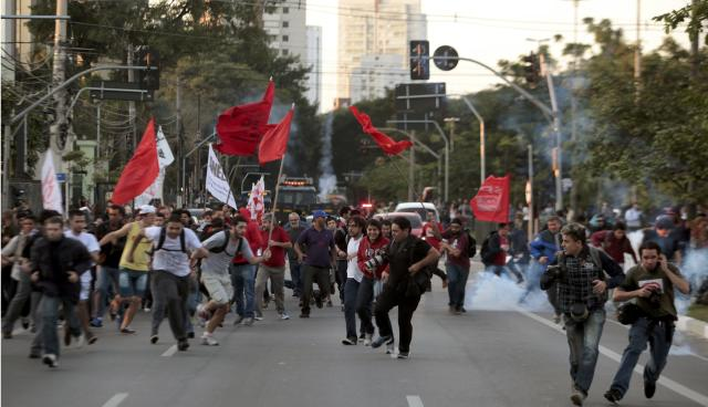 People run away from tear gas fired by police during the fifth day of metro worker's protest in Sao Paulo June 9, 2014. A court set a 500,000 reais penalty ($223,000) for each day metro workers' union membersstay off work from Monday and also declared the strike illegal, complicating preparations for the World Cup opening match. REUTERS/Stringer/Brazil (BRAZIL - Tags: BUSINESS EMPLOYMENT SOCCER SPORT TRANSPORT CIVIL UNREST WORLD CUP)