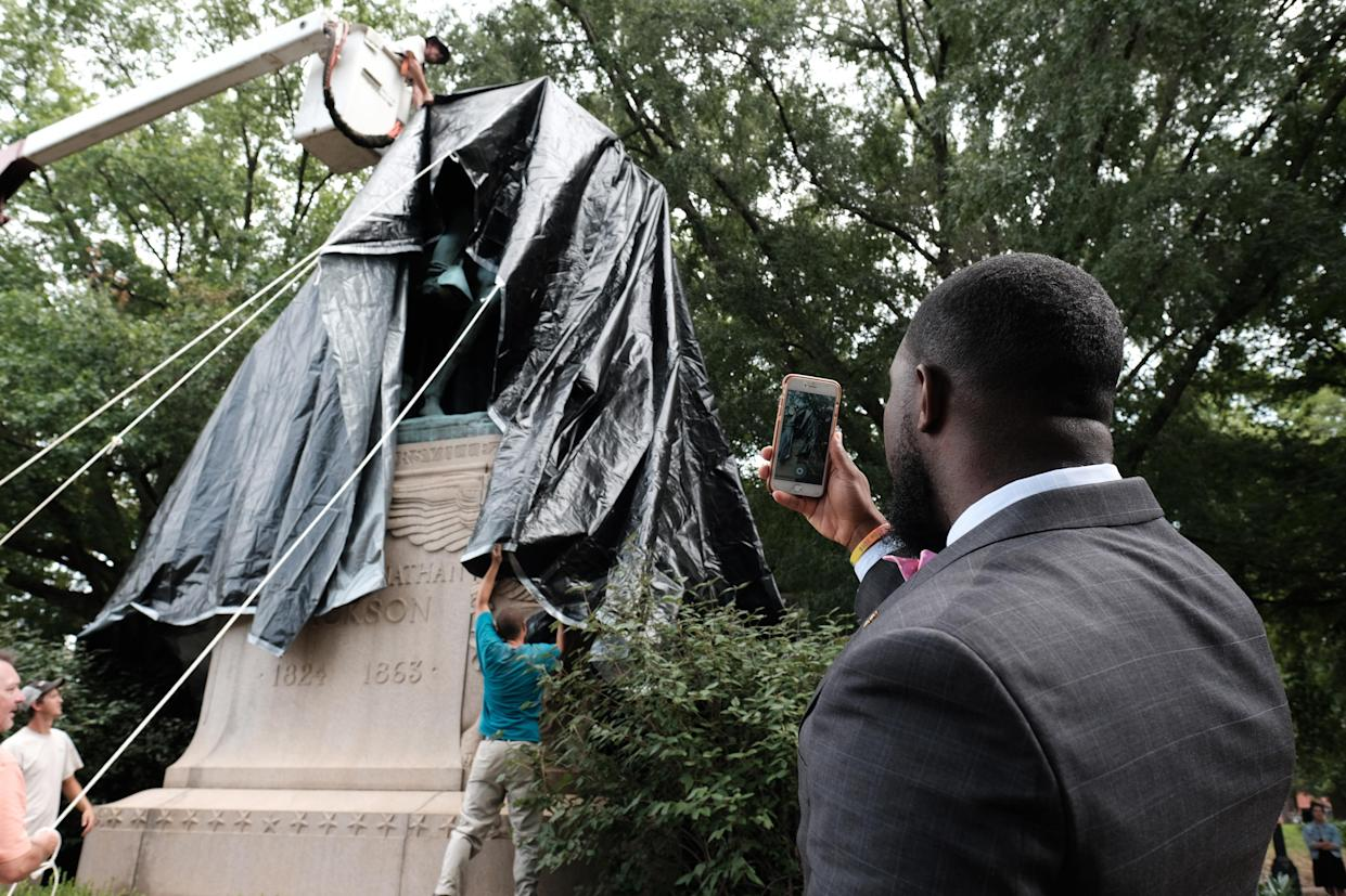 The statue of Confederate Gen. Stonewall Jackson is shown covered in black tarp as Wes Bellamy, the vice mayor of Charlottesville, looks on in Charlottesville, Va, Aug. 23, 2017. (Photo: Justin Ide/Reuters)