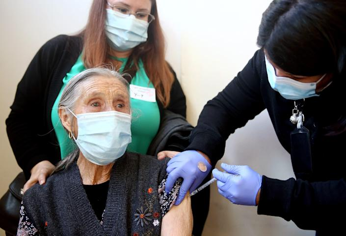 An 86-year-old woman receives her first dose of the Pfizer COVID-19 vaccine at a clinic targeting minority community members at St. Patrick's Catholic Church on April 9, 2021, in Los Angeles. St. John's Well Child and Family Center is administering COVID-19 vaccines in churches across South L.A. in an broad effort to bring vaccines to minority communities.