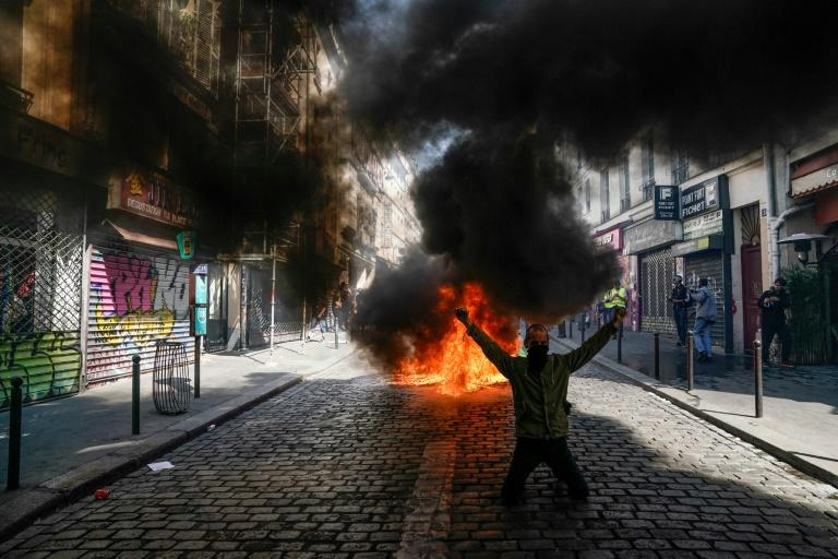 A protester in front of a fire during an anti-government demonstration in Paris