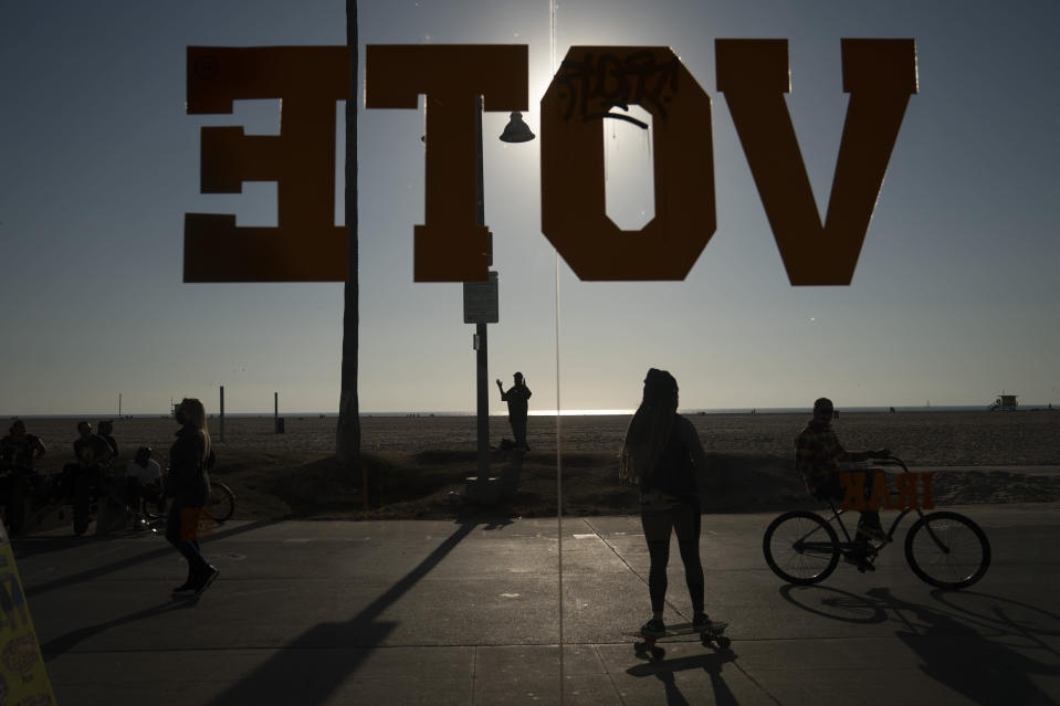 A vote sign is posted on the window of a shoe store on the Venice Beach Boardwalk in Los Angeles, Wednesday, Oct. 28, 2020. (AP Photo/Jae C. Hong)