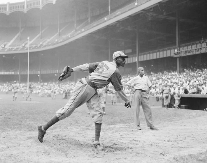 Kansas City Monarchs pitching great Leroy Satchel Paige warms up at New York's Yankee Stadium August 2, 1942