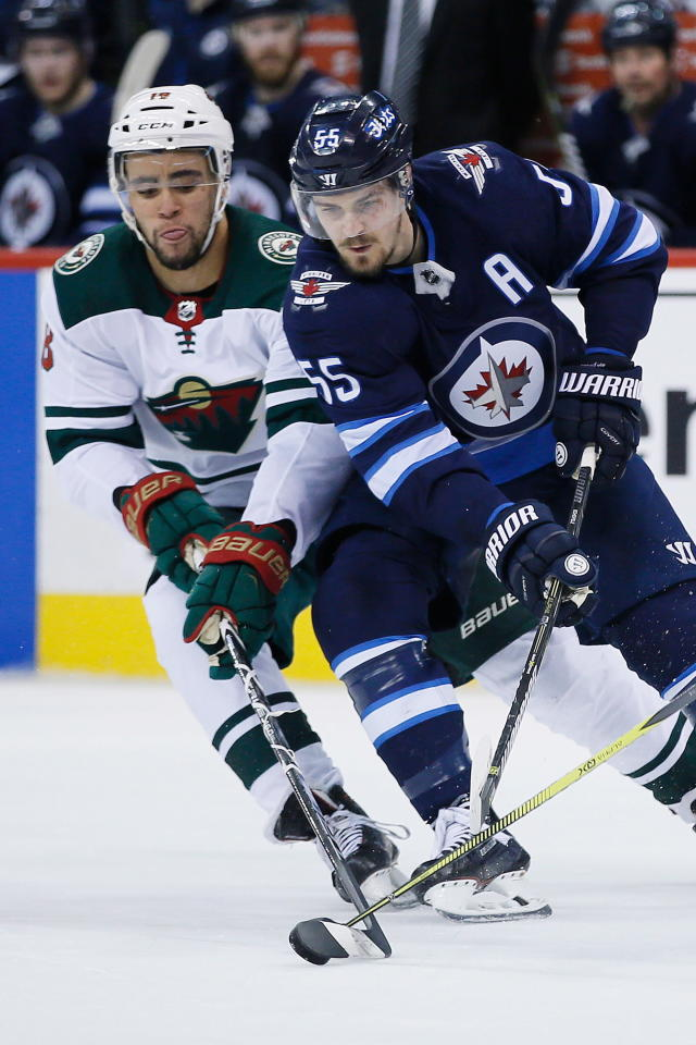 Minnesota Wild's Jordan Greenway (18) steals the puck from Winnipeg Jets' Mark Scheifele (55) during the second period in Game 5 of an NHL hockey first-round playoff series in Winnipeg, Manitoba, Friday, April 20, 2018. (John Woods/The Canadian Press via AP)