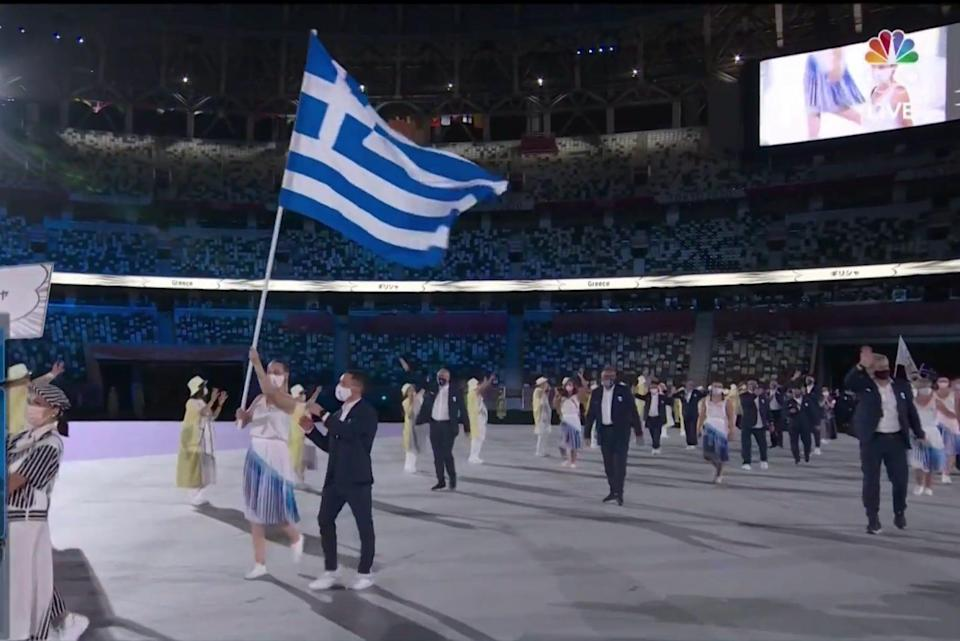 Athletes from Greece wave their country's flag to start the Parade of Nations.