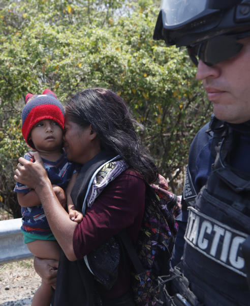 A Central American migrant woman and her son walk with a Mexican Federal Police agent as they are taken into custody on the highway to Pijijiapan, Mexico, Monday, April 22, 2019. Mexican police and immigration agents detained hundreds of Central American migrants Monday in the largest single raid on a migrant caravan since the groups started moving through Mexico last year. (AP Photo/Moises Castillo)