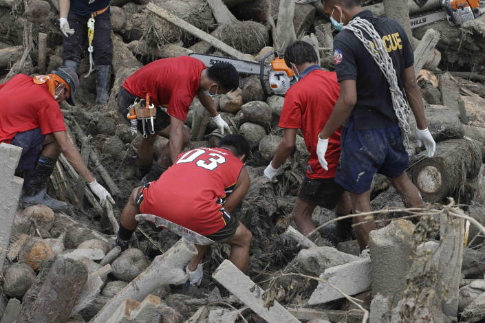 Rescuers work to retrieve another flash flood victim from the debris of Tuesday's Typhoon Bopha at New Bataan township, Compostela Valley in southern Philippines Friday Dec. 7, 2012. Rescuers were digging through mud and debris Friday to retrieve more bodies strewn across a farming valley in the southern Philippines by a powerful typhoon. (AP Photo/Bullit Marquez)
