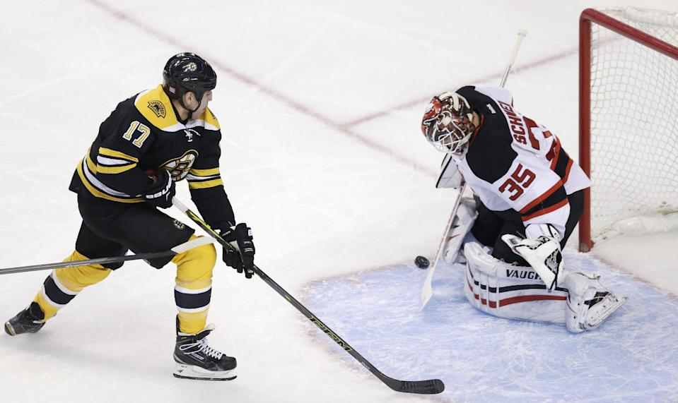 New Jersey Devils goalie Cory Schneider (35) makes a save on a shot by Boston Bruins left wing Milan Lucic (17) during the first period of an NHL hockey game in Boston, Monday, Nov. 10, 2014. (AP Photo/Charles Krupa)