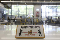 "A social distancing sign is seen on a table to help curb the spread of the coronavirus at No Brand Burger in Seoul, South Korea, Sunday, Sept. 13, 2020. The signs read: ""Social distance and Delicious distance one meter."" (AP Photo/Ahn Young-joon)"
