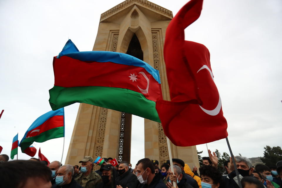Azerbaijanis wave national flags as they celebrate entry of troops in Nagorno-Karabakh's Aghdam region in Baku, Azerbaijan, Friday, Nov. 20, 2020. Units of the Azerbaijani army on Friday morning entered the Aghdam region, a territory ceded by Armenian forces in a cease-fire agreement that ended six weeks of heavy fighting over the separatist region of Nagorno-Karabakh, Azerbaijan's Defense Ministry said. (AP Photo/Aziz Karimov)