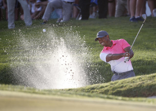 Tiger Woods hits out of a bunker on the 18th hole during the second round of the Honda Classic golf tournament, Friday, Feb. 23, 2018, in Palm Beach Gardens, Fla. (AP Photo/Wilfredo Lee)