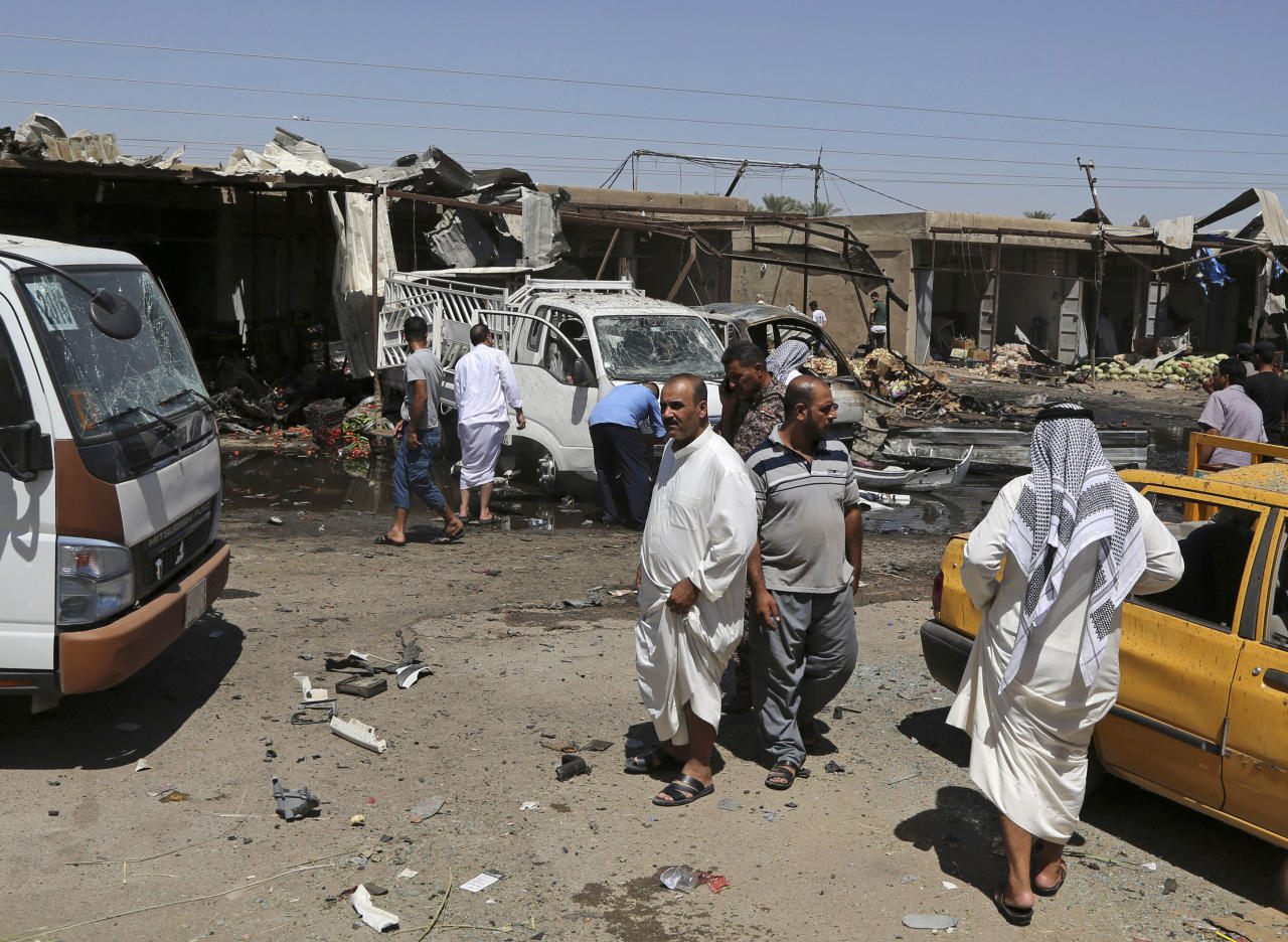Civilians gather at the scene of a suicide car bombing at an outdoor market in a Shiite-dominated district in northeastern Baghdad, Iraq, Tuesday, July 12, 2016. The bomb on Tuesday, killed at least 10 people and injured tens of others, officials said, as government forces deployed across much of the Iraqi capital in preparation for a major military parade later this week. The developments came on the heels of two large-scale attacks claimed by the Islamic State group that killed more than 300 people last week. (AP Photo/Karim Kadim)