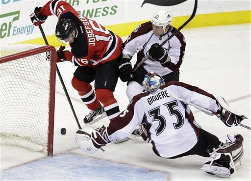 Colorado Avalanche goalie Jean-Sebastien Giguere (35) reaches for the puck as New Jersey Devils' Jacob Josefson (16), of Sweden, tries to score past Colorado Avalanche's Matt Hunwick (22) during the second period of an NHL hockey game in Newark, N.J., Thursday, March 15, 2012. (AP Photo/Mel Evans)