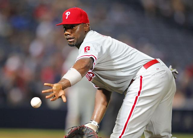 Philadelphia Phillies first baseman Ryan Howard (6) tosses to relief pitcher Jonathan Papelbon (58) for the out of Atlanta Braves Tommy La Stella in the ninth inning of a baseball game Tuesday, June 17, 2014, in Atlanta. (AP Photo/Todd Kirkland)