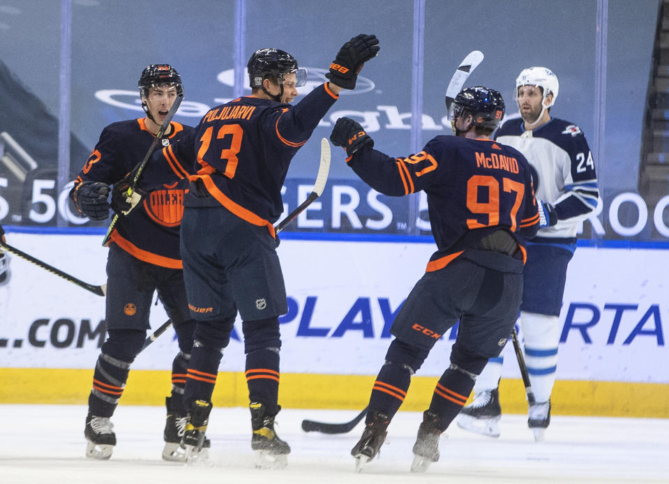 Edmonton Oilers' Ryan Nugent-Hopkins (93) celebrates a goal by Jesse Puljujarvi (13) and 500th career point by Connor McDavid (97), against the Winnipeg Jets during the first period of an NHL hockey game Wednesday, Feb. 17, 2021, in Edmonton, Alberta. (Jason Franson/The Canadian Press via AP)