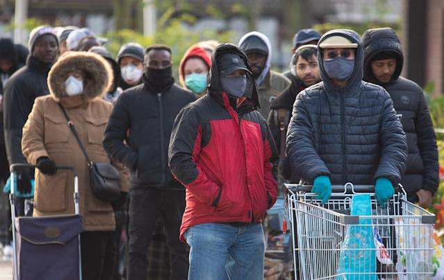 The new total amount of confirmed cases in the UK has been released by the government – as people in face masks queue at Aldi. (PA Images)