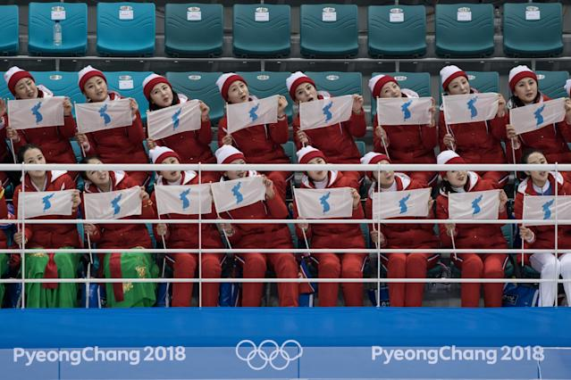 <p>North Korean cheerleaders wave flags showing a unified Korean peninsula as they perform following the women's preliminary round ice hockey match between the unified Korea team and Switzerland at the Pyeongchang 2018 Winter Olympics, at the Gangneung Ice Arena in Gangneung on February 10, 2018. </p>