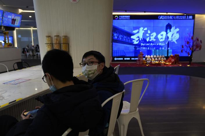 """Youths wearing masks to protect from the coronavirus chat near a screen showing a trailer for the film """"Days and Nights in Wuhan"""" in a cineplex in Wuhan in central China's Hubei province on Friday, Jan. 22, 2021. China is rolling out the state-backed film praising Wuhan ahead of the anniversary of the 76-day lockdown in the central Chinese city where the coronavirus was first detected. (AP Photo/Ng Han Guan)"""