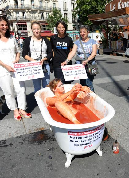 "An activist from the association ""People for the Ethical Treatment of Animals"" (PETA) bathes in a bathtub fed up with tomato sauce ""to symbolise a bloodshed"",as pedestrians look on, on August 8, 2012, at the Bastille square in Paris, to denounce (boards at second ground) a European Union project. The European Commission plans to push to the end of 2013 the ban on the cosmetic industry to use in their products ingredients tested on animals.