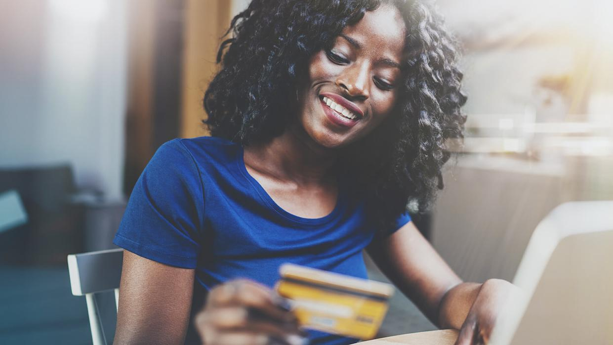 Woman shopping online through laptop using credit card at home.