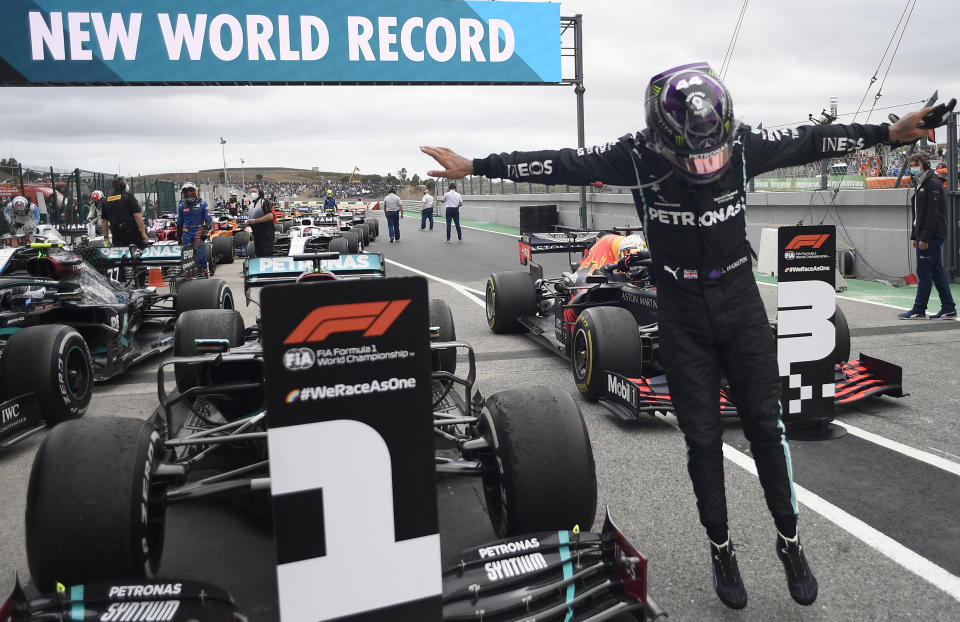Mercedes driver Lewis Hamilton of Britain jumps out of his car after his record breaking win during the Formula One Portuguese Grand Prix at the Algarve International Circuit in Portimao, Portugal, Sunday, Oct. 25, 2020. (Jorge Guerrero, Pool via AP)