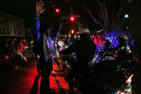 A man raises his hands while attempting to block the movement of a group of motorcycle police during a demonstration against the grand jury decision in the Ferguson, Missouri shooting of Michael Brown in San Francisco, California November 28, 2014. REUTERS/Stephen Lam