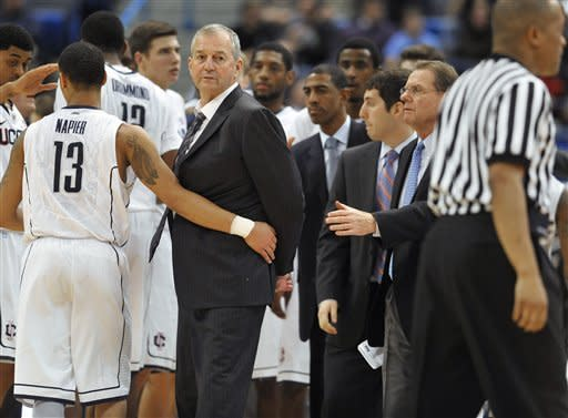 Connecticut head coach Jim Calhoun, second from left, is held back by Connecticut's Shabazz Napier (13) during a timeout in the first half of an NCAA college basketball game against Fairfield in Hartford, Conn., Thursday, Dec. 22, 2011. (AP Photo/Jessica Hill)
