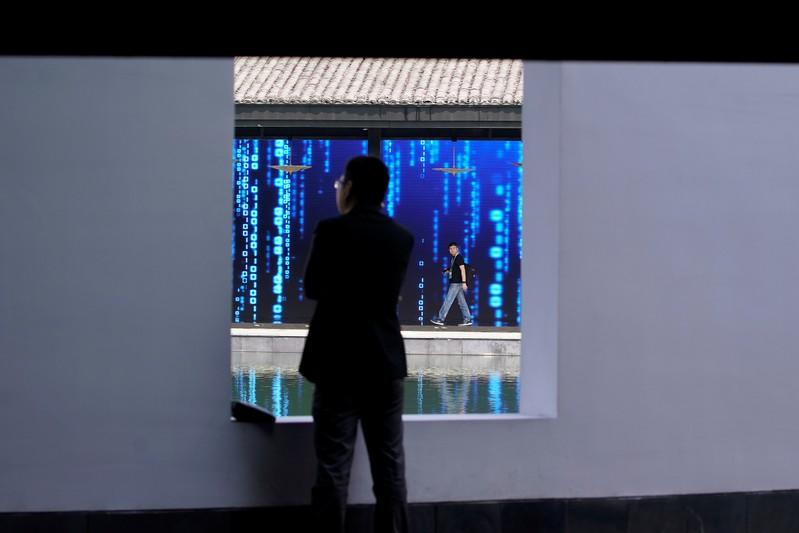A man walks in front of a screen at the World Internet Conference (WIC) in Wuzhen