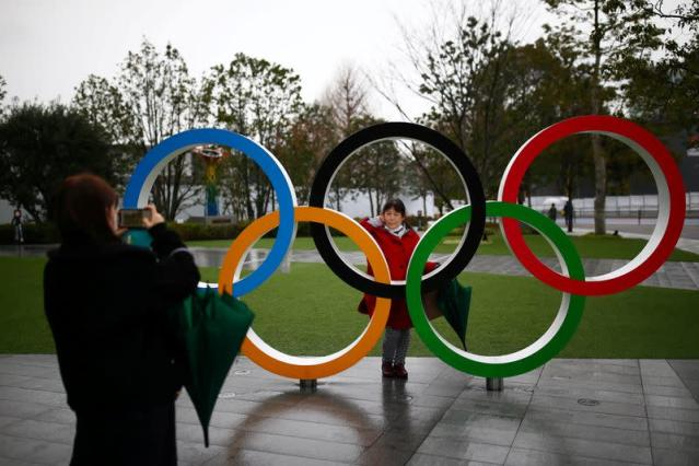 A woman poses for a photo through The Olympic rings in front of the Japan Olympics Museum in Tokyo