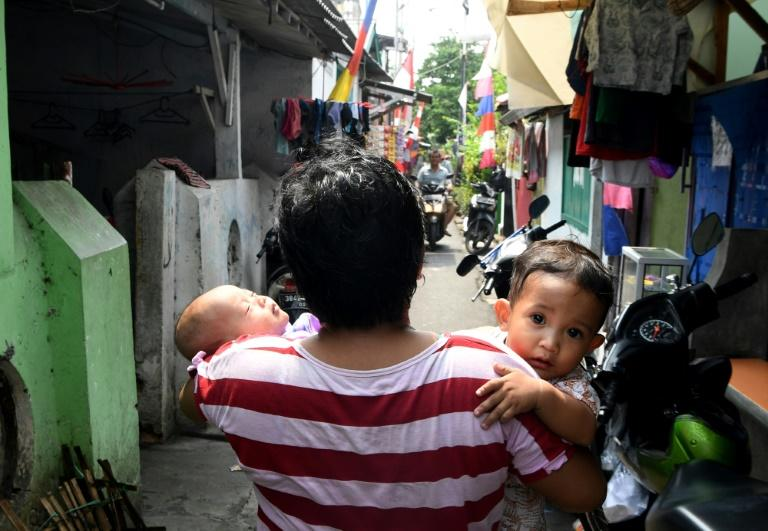 An Indonesian woman carries her children along the neighbourhood where Dedy Sukma, who Indonesian police accused of stealing a motorcycle before he was shot and killed, used to live in Jakarta