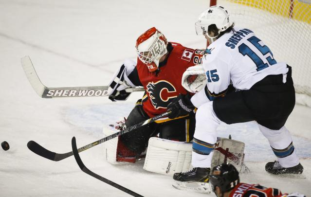 San Jose Sharks' James Sheppard, right, chases a rebound from Calgary Flames goalie Reto Berra, from Switzerland, during the second period of an NHL hockey game Tuesday, Nov. 12, 2013, in Calgary, Alberta. (AP Photo/The Canadian Press, Jeff McIntosh)
