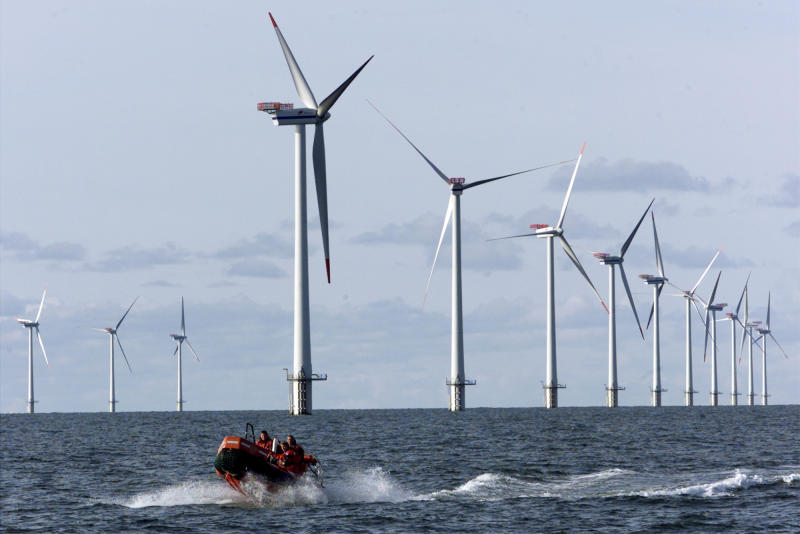 FILE - This Oct. 30, 2002 file photo shows a speed boat passing by offshore windmills in the North Sea offshore from near Esbjerg, Denmark. On Wednesday Feb. 5, 2014, Oregon's Governor, John Kitzhaber and other officials announced plans to develop a similar farm, as the West Coast's first offshore wind energy farm. (AP Photo/Heribert Proepper, file)