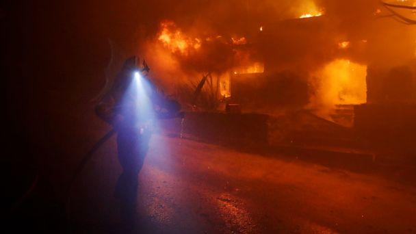PHOTO: A firefighters gets in position to hose down flames as a home burns in the Getty fire area along Tigertail Road in Los Angeles, Oct. 28, 2019. (Marcio Jose Sanchez/AP, FILE)