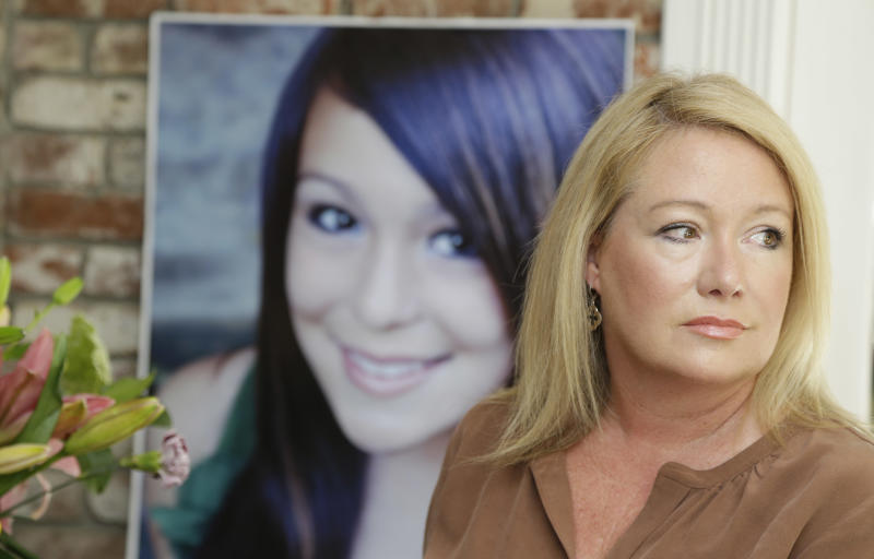 Sheila Pott poses with a portrait of her daughter Audrie in Los Altos, Calif., Thursday, May 23, 2013. Audrie Pott committed suicide in September 2012 after being sexually assaulted by three boys during a house party in Saratoga, Calif. Photos of the incident were circulated around Pott's high school prompting the teenager to hang herself in a bathroom at home. (AP Photo/Marcio Jose Sanchez)