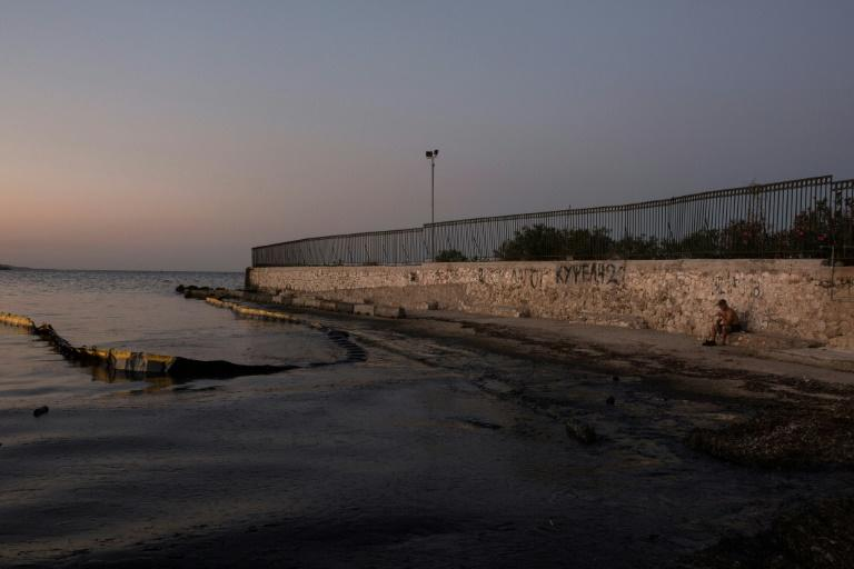 An oily sea on a beach near Athens, five days after the sinking of a tanker, has triggered criticism from environmental groups over the Greek government's response to the spill