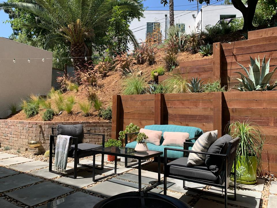 """<div class=""""caption""""> James describes the initial state of his yard as a super muddy dirt pit. Refinishing the space with huge pavers and large-scale rock hardscaping created the major refresh. The team wanted to make sure the space fits its location and kept the West Coast vibes with various shades of tan and lots of <a href=""""https://www.architecturaldigest.com/story/best-indoor-cacti?mbid=synd_yahoo_rss"""" rel=""""nofollow noopener"""" target=""""_blank"""" data-ylk=""""slk:cacti"""" class=""""link rapid-noclick-resp"""">cacti</a> and succulents. </div> <cite class=""""credit"""">Photography: Michael Clifford</cite>"""