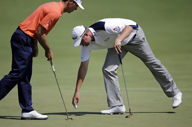 Marc Leishman, right, of Australia, retrieves his ball in front of Billy Horschel after making a birdie on the 11th green during the second round of the Quicken Loans National PGA golf tournament, Friday, June 27, 2014, in Bethesda, Md. (AP Photo/Patrick Semansky)