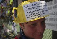 Hialeah resident Alison Kairuz is shown after pinning her hand-made sign to the fence in support of families and friends who lost love ones at the memorial site for victims of the partially collapsed South Florida condo building Champlain Towers South in Surfside, Fla., Sunday, July 4, 2021. (Carl Juste/Miami Herald via AP)