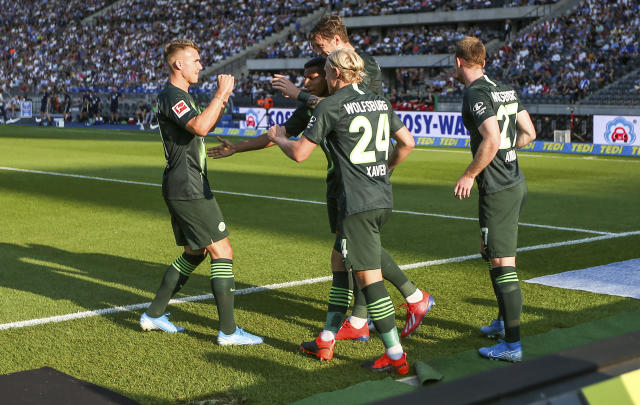 Wolfsburg players celebrate a goal by Wout Weghorst during the German Bundesliga soccer match between VfL Wolfsburg and Hertha BSC Berlin in Berlin, Germany, Sunday, Aug. 25, 2019. (Andreas Gora/dpa via AP)