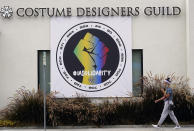 A woman walks past a poster advocating union solidarity in front of a Costume Designers Guild office building, Monday, Oct. 4, 2021, in Burbank, Calif. The International Alliance of Theatrical Stage Employees (IATSE) overwhelmingly voted to authorize a strike for the first time in its 128-year history. (AP Photo/Chris Pizzello)