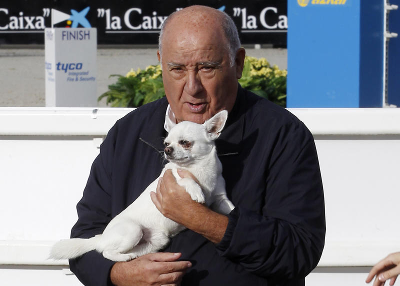 In this July 28, 2013 photo, Amancio Ortega Gaona, founding shareholder of Inditex fashion group, best known for its chain of Zara clothing and accessories retail shops, holds a dog during the Casas Novas International Jumping Show in Arteixo, A Coruña, in the Galicia region of northwest Spain. Amancio Ortega, has been named as the richest person in Europe, and the second richest in the whole world. (AP Photo/Iago Lopez)
