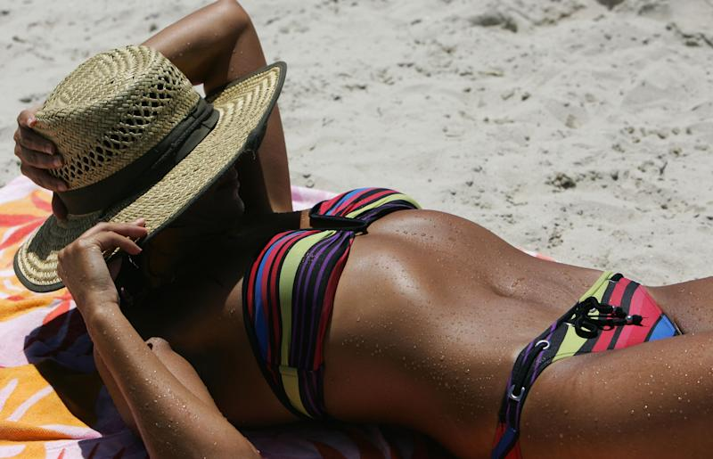 A tanned woman bakes in the sun on a Sydney beach.